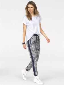 Weiße Sneaker sehen in Kombination mit lässiger Stoffhose und schlichtem weißen T-Shirt super aus.